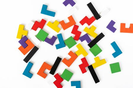 Background from colorful different shapes wooden blocks on white background. Natural, eco-friendly toys for children. Creative, logical thinking concept. Flat lay. Copy space.