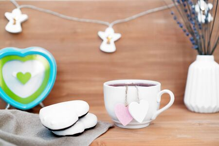 Heart shaped tea bag in white cup of tea with ginger coocies - cute love declaration on wooden background, selective focus. Valentines day concept. Mug of tea for two lovers honeymoon wedding morning surprise breakfast