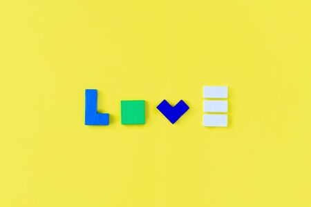 Word LOVE made from colorful wooden bricks on yellow background. Parents love and kids game concept. Top view, flat lay.