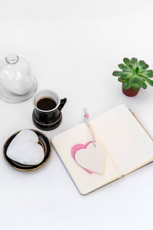 Valentine's Day composition. Female desktop with cup of coffee and plate with heart shaped ginger cookie on white background. Valentines Day celebration concept