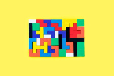 Colorful wooden blocks of different shapes puzzles on yellow background. Natural, eco-friendly toys. Creative, logical thinking concept. Background with geometric shapes wooden blocks.