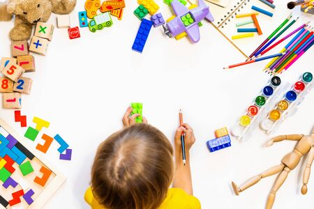 Prescool boy drawing on floor on paper. Kid play with blocks, plane and cars. Educational toys for preschool and kindergarten child, Child at home or daycare. Top view Stockfoto