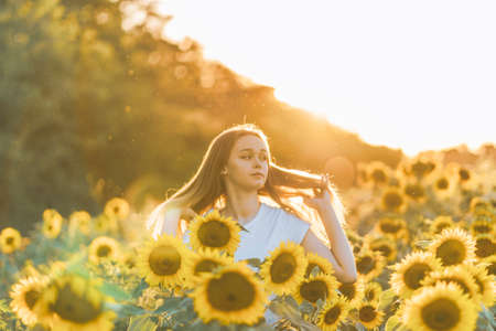 Young beautiful woman smiling and having fun in a sunflower field on a beautiful summer day.
