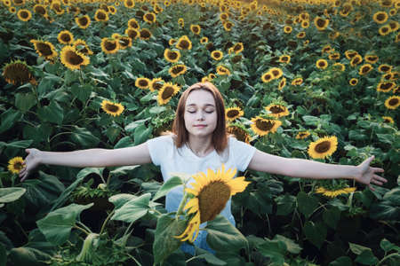 Young beautiful woman smiling and having fun in a sunflower field on a summer day with open arms.