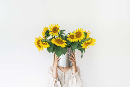 Beautiful young woman in linen dress holds sunflowers bouquet in a tin bucket on white background.