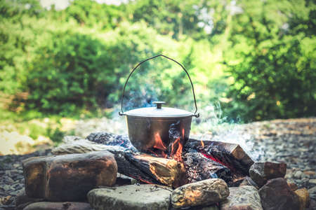 Traveling, tourism, picnic cooking, cooking in a cauldron on the fire, boiling pot at the campfire on picnic.
