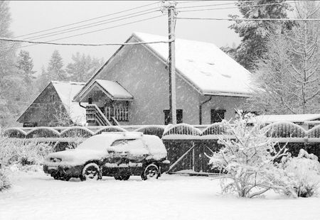 The car in a court yard of a country house under a snowfall photo