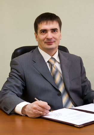 Portrait of the businessman sitting on the workplace with official papers Stock Photo - 4558998