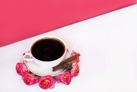 Cup of coffee with cinnamon on a pink background with flowers