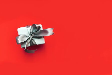 White gift box with silver flying on a red background, with an empty place for text. 스톡 콘텐츠