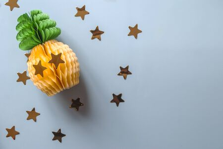Paper pineapple with large gold confetti on a blue background. Festive background. Top view.