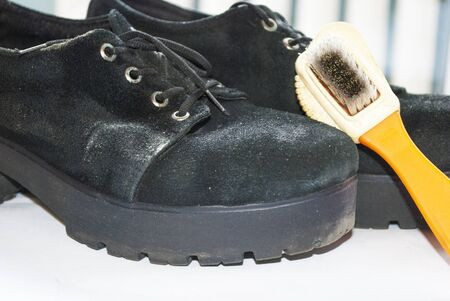 Old worn suede shoes and shoe brush Stock Photo