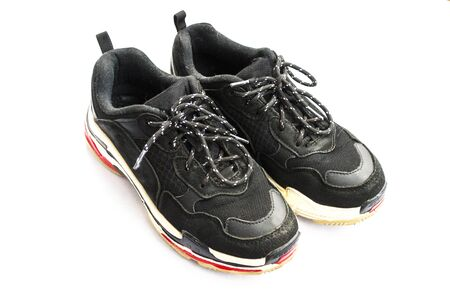 Old well-worn sports black sneakers on a white background. Isolate 版權商用圖片