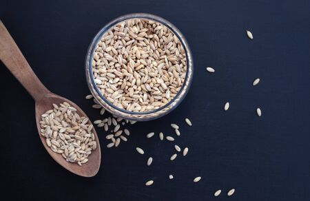 Barley porridge in a glass jar on a blue table top view, wooden spoon Zdjęcie Seryjne