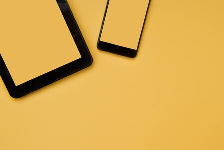 Black tablet and black phone on an orange background. Place for text. Top view. Flat lay