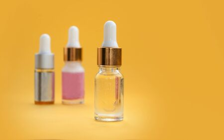 Three transparent bottle with cosmetic serum closeup on an orange background.