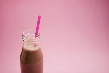 Glass bottle of cocoa with a pink straw on a pink background. Place for text. Flat lay. Top view.