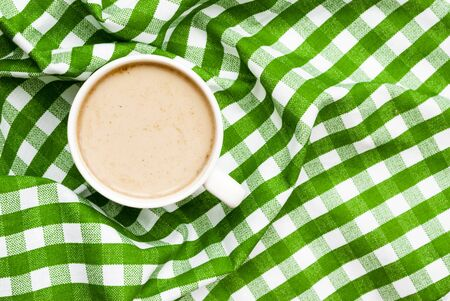 Cup of tasty coffee with milk on a green background, place for text. Top view.