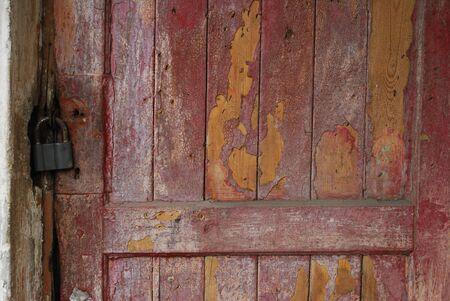 Close-up. Old dark red shabby door with padlock Stock Photo