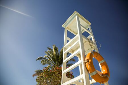 A white observation lifeguard tower near the palms with sun rays and beautiful sky