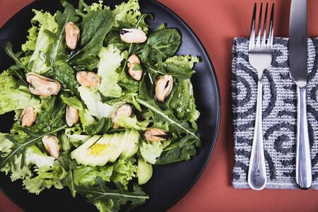 Healthy fresh salad with mussels, avocado, lettuce and arugula . Top view. Diet conception