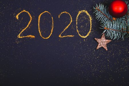 Christmas, New Year composition. Glittered number 2020, Christmas bauble and fir branches on black background. Flat lay, top view festive holiday mockup.