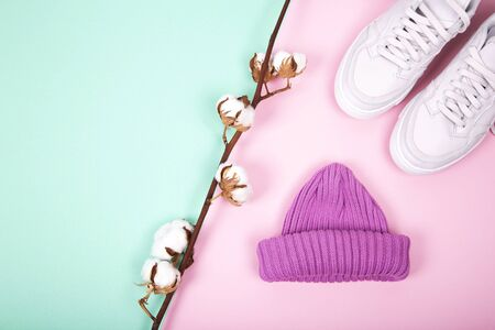 One knitted purple hat and modern pink sneakers with cotton branch. Flat lay composition on turquoise and pink background. Layout and with copy space