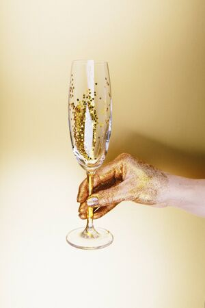 Woman hand holding glasses of champagne on golden background.