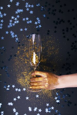 Woman hand holding glasses of champagne on festive background. Archivio Fotografico