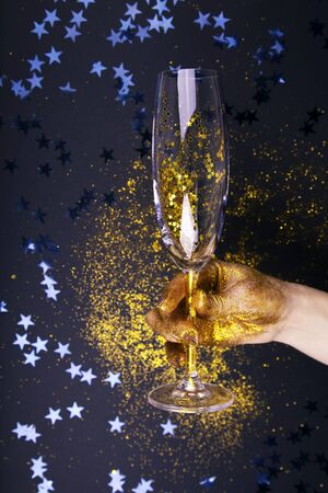 Woman hand holding glass of champagne on festive black background. Archivio Fotografico