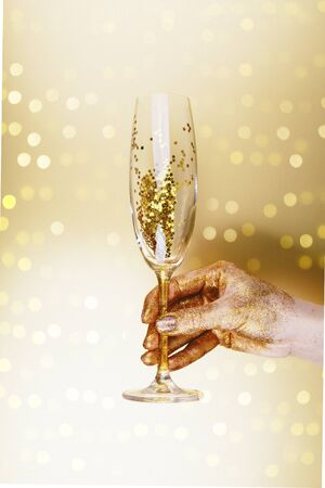 Woman hand holding champagne glass on festive golden background.