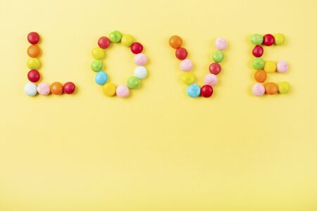 Mixed of colorful candies on yellow background. Love note