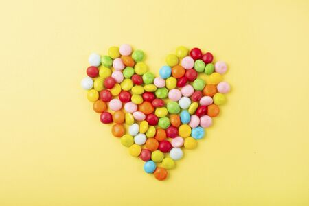 Mixed of colorful candies on yellow background. Heart shape