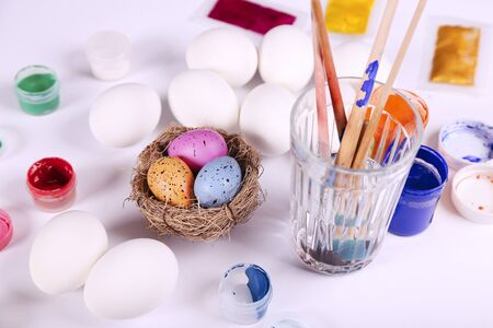 Easter eggs in the nest and chicken empty eggs and tools for painting near by Stock Photo