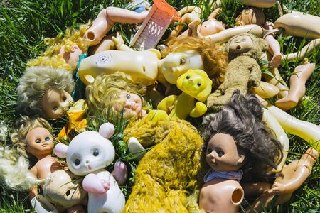 Many old broken dolls and toys on the grass thrown like a garbage