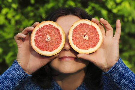 Funny playful woman holding halves of citrus fruits against her eyes over nature background