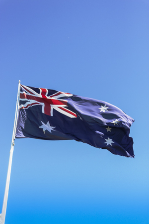 Flag of Australia flying high against a sunny clear sky