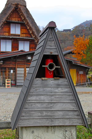 Hida, Japan - 2010: Fire hydrant pipe with gassho-style foof top in Shirakawago Village