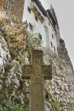 Bran, Romania - 2013: Stone cross at gardens of Bran Castle