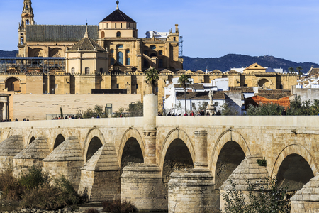 Cordoba, Spain - Dec 2018: Picturesque view of the Roman bridge of Cordoba facing Mosque-Cathedral of Cordoba