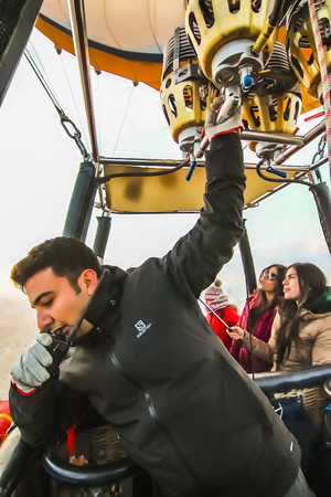Cappadocia, Turkey - Dec 2015: A hot air balloon pilot with one hand on walkie-talkie communicating and the other on the burner