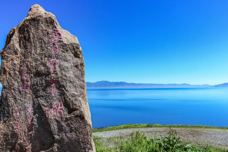 Stone engraved signage at Sayram Lake in Xinjiang, China. (English translation - Sailimu Lake or Sayram Lake) Imagens