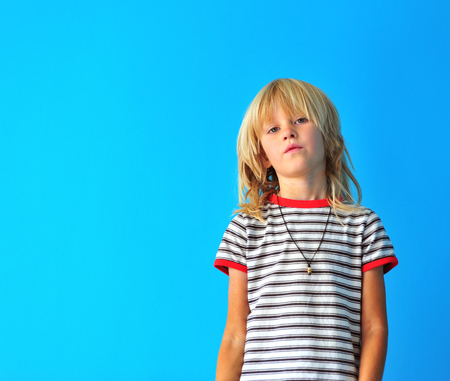 Portrait of a cute blonde boy at blue wall background