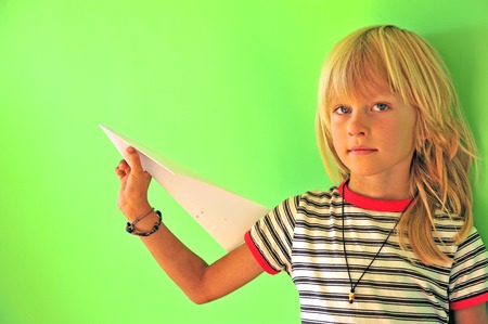 Little boy with paper airplane at green wall background