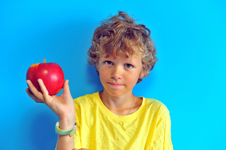 Shaggy boy with an apple at blue wall on background