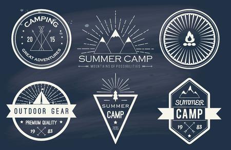 Set of vintage summer camp badges and other outdoor emblems and labels on blackboard