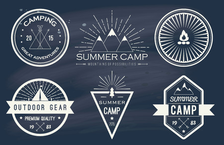 Set of vintage summer camp badges and other outdoor emblems and labels on blackboard