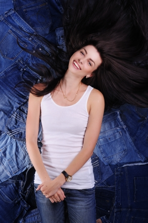 сooking: happy girl with long dark hair flying in a white shirt on jeans background