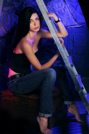 beautiful young brunette woman sitting near the ladder in jeans and a top on jeans background with screen photo