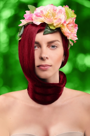 hair tied: beautiful red-haired girl in a wreath of pink tsetov with hair tied in a knot around the neck on a green background with bokeh  Stock Photo